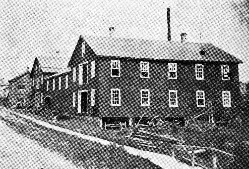 A black and white halftone image of a two storey wooden industrial building on a dirt road with white-trimmed windows and doors, an empty lot with debris in the foreground and other wooden buildings in the background.