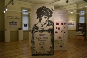A museum exhibit inside a wooden-floored room with high windows, the panel facing has an ink image of a 19th century woman, with maps and artifacts on other panels and against the walls.