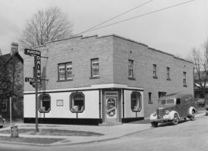 A black and white photograph of a brick shop with a corner-facing door, its façade has contrasting lines and octagonal windows, an early mid-20th century delivery van is parked on the street.
