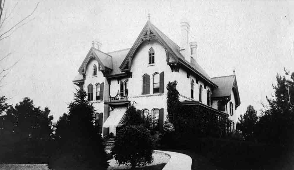A black and white photograph of a mansion with a dark roof and elaborate trim, bushes decorate the grounds.