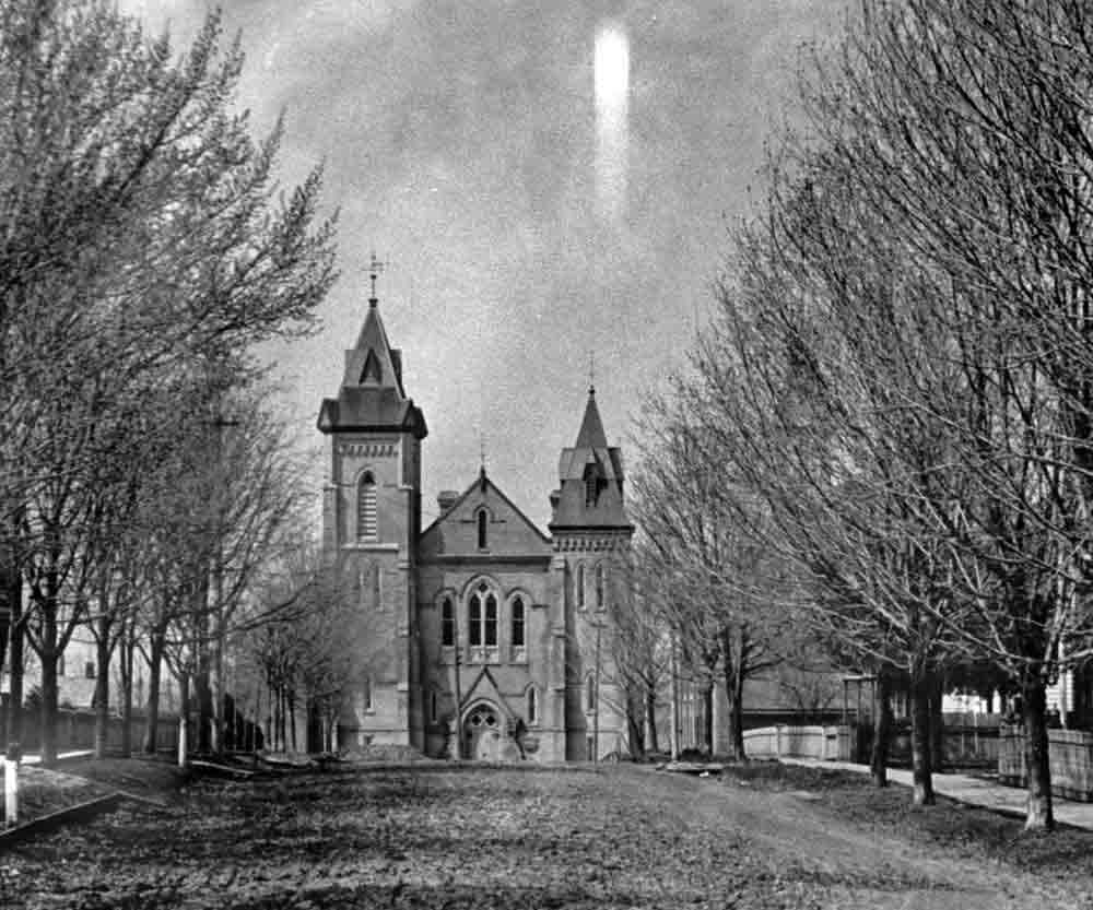 A black and white photograph of a tree-lined dirt road leading to a large church with two towers of different heights.