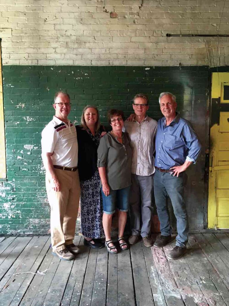 A photograph of two women and three men standing against an old brick wall, painted green and white.