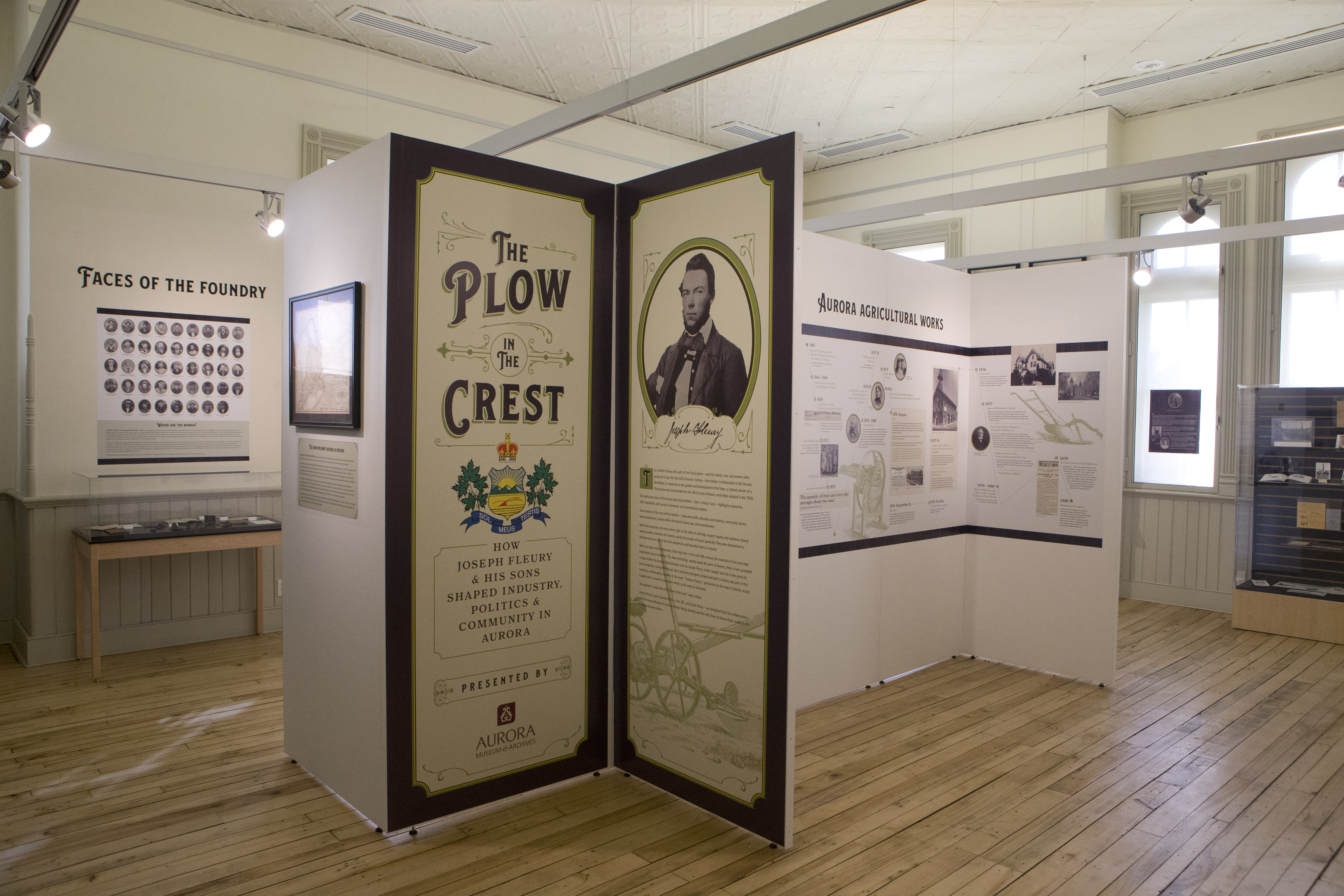 A museum exhibit in a wood-floored room with tall windows.