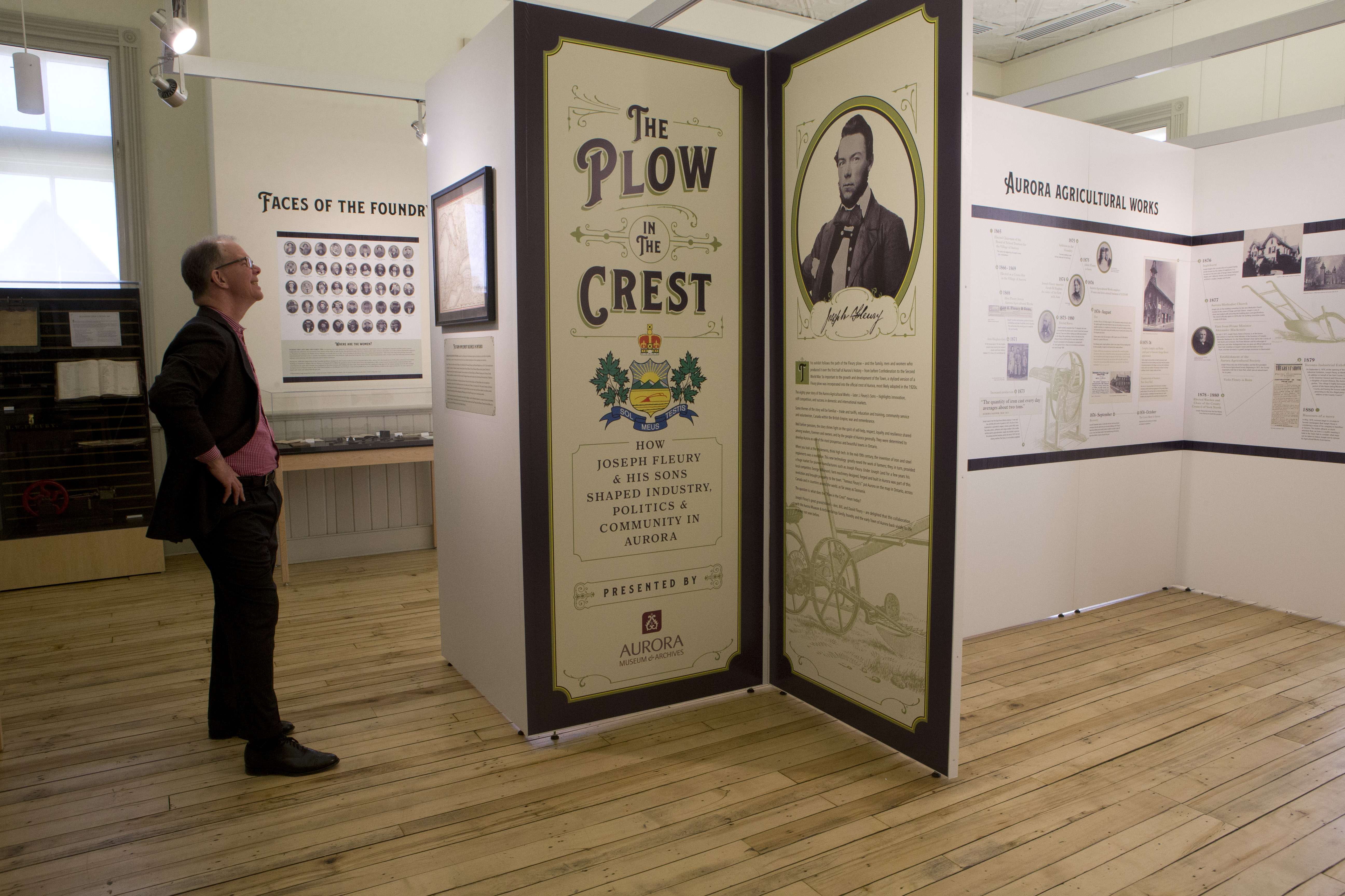 A man is smiling while reading a part of a museum exhibit about his family's legacy.