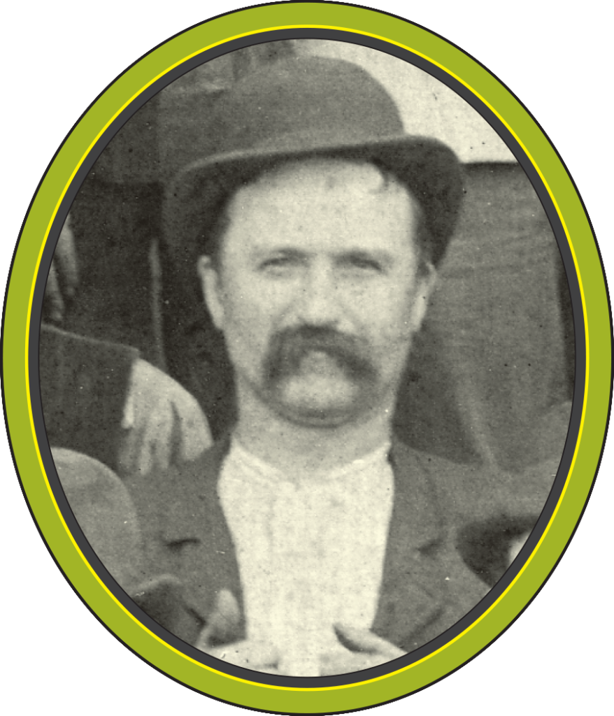 A black and white photograph of a man with a long moustache and a tilted bowler hat, holding his lapels.