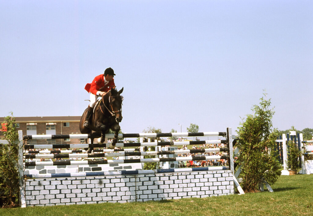 A colour photograph of a rider and horse jumping over black and white fence obstacle as part of a competition