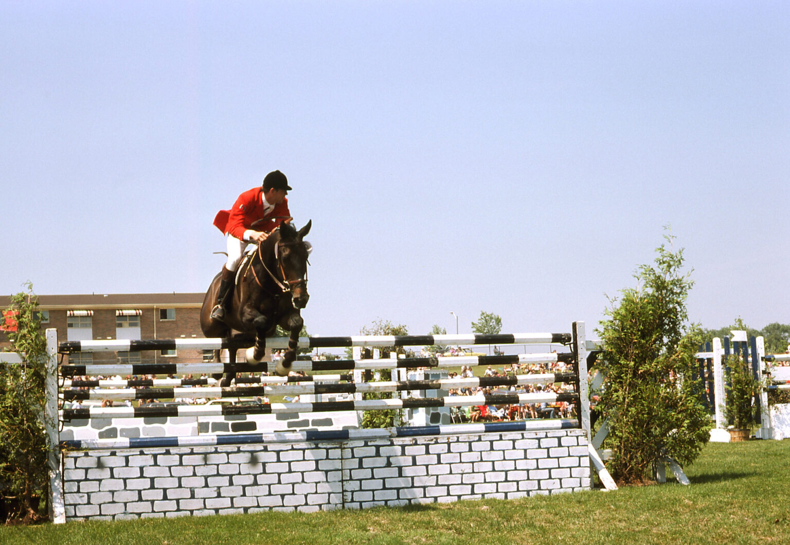 A colour photograph of a rider and horse jumping over a fence.