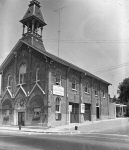 A black and white photograph of a brick building with a semicircular arches and a bell tower on the corner of a street.
