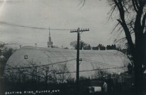 A black and white photograph of a white semi-cylindrical building with small windows on its end, power lines cross the foreground and a church steeple rises behind