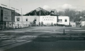 A black and white photo of an arena building with a peaked roof that has been burned from the inside by fire.