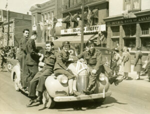 A black and white photo of WWII service people riding on the outside of a car travelling in a parade.