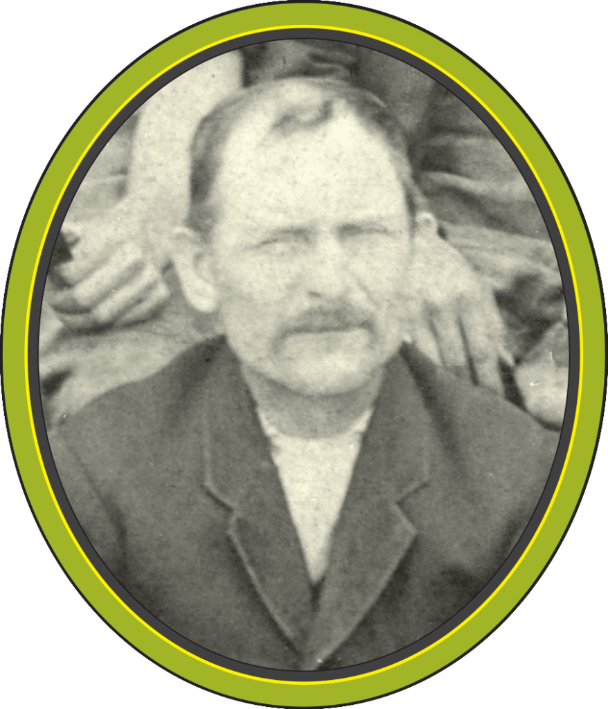 A black and white photograph of a man with a moustache and a receding hairline, squinting.
