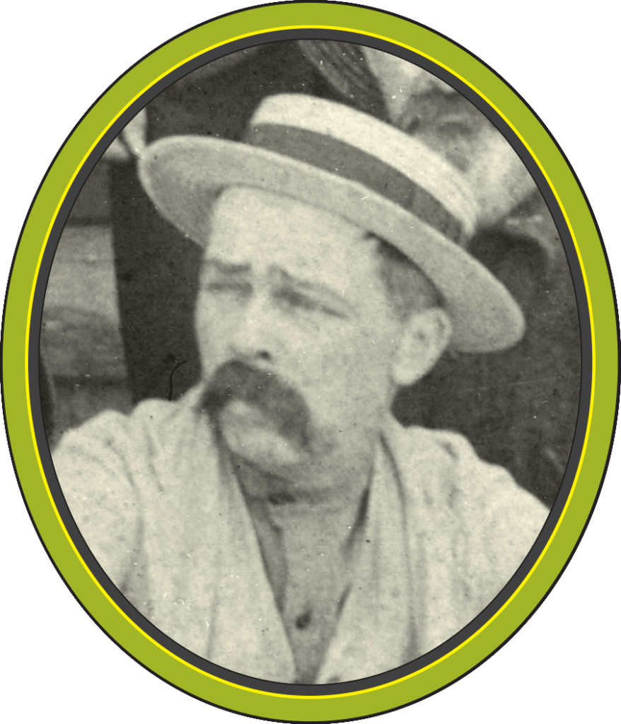 A black and white photograph of a man with a moustache and a boater hat, looking to the left.