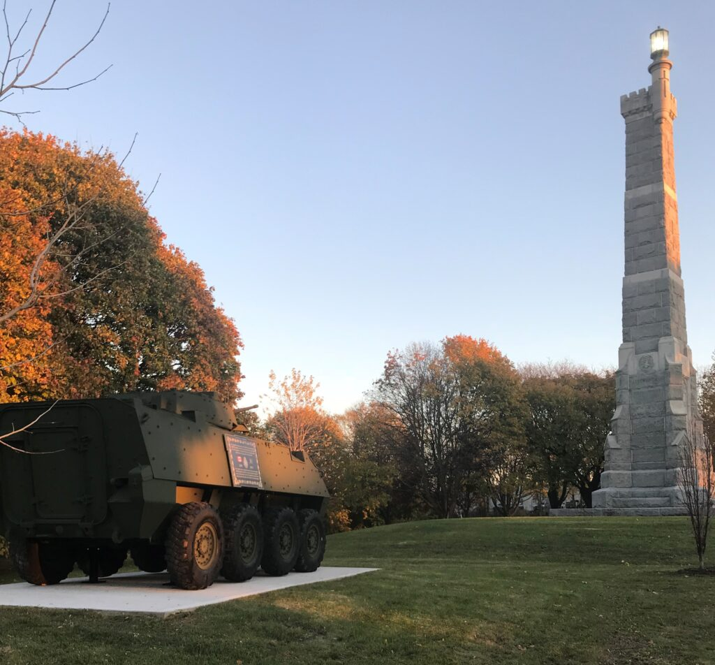 A colour photograph of a tall grey stone memorial with a lantern atop, in a treed park to the right of an eight-wheeled armoured vehicle with a plaque affixed to its side, the scene is bathed in early evening sunlight.