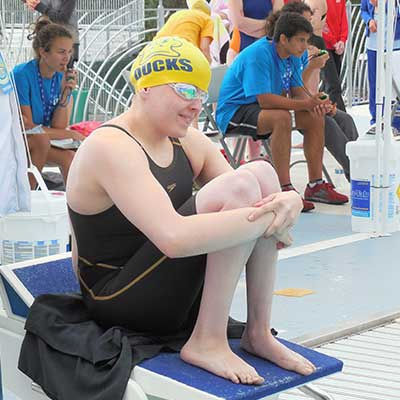 A photograph of a swimmer in a yellow cap and goggles, sitting with their knees up.