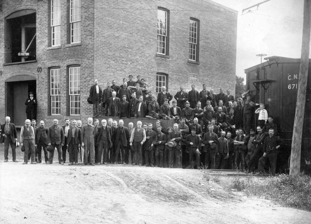 A black and white photograph of a group of dark-clad men standing outside a brick factory building with tall windows.