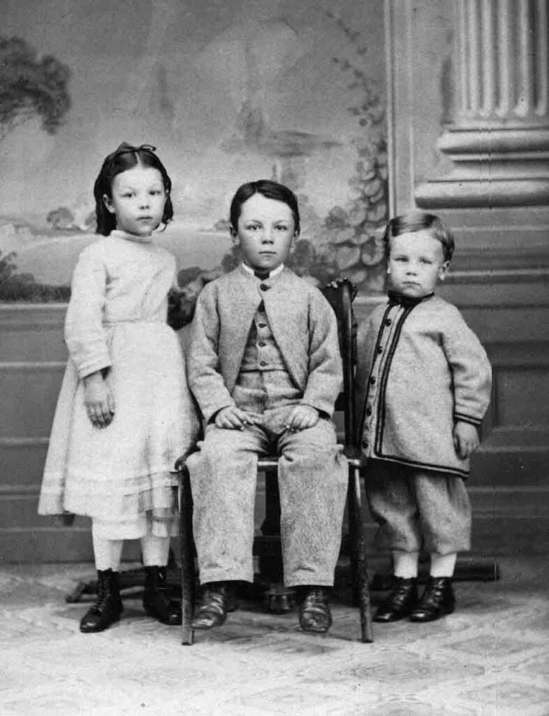 A black and white portrait photograph of a young girl and two young boys, the elder boy is sitting in the middle.