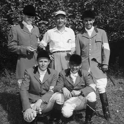 A black and white photograph of an equestrian team in uniform.