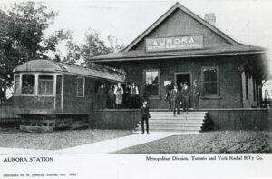 A postcard with a black and white photograph of a small brick train station with a passenger car parked beside it, and a group of people on the raised platform, stairs and front walkway. The station is described in text underneath.