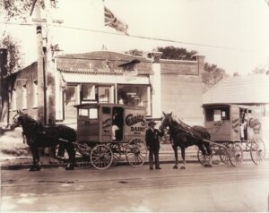 A black and white photograph of a one-storey brick shop with two horse-drawn dairy carriages in front, one man stands holding a horse, another man in each carriage.