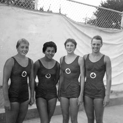 A black and white photo of four women in competitive swimsuits.