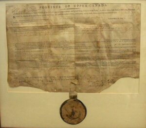 A framed document on parchment with circular seal hanging from it.