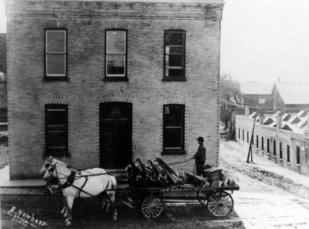 A black and white photograph of a horse-drawn carriage in front of a brick industrial building.