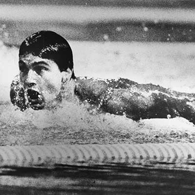A black and white action photograph of a swimmer taking a breath during a race.