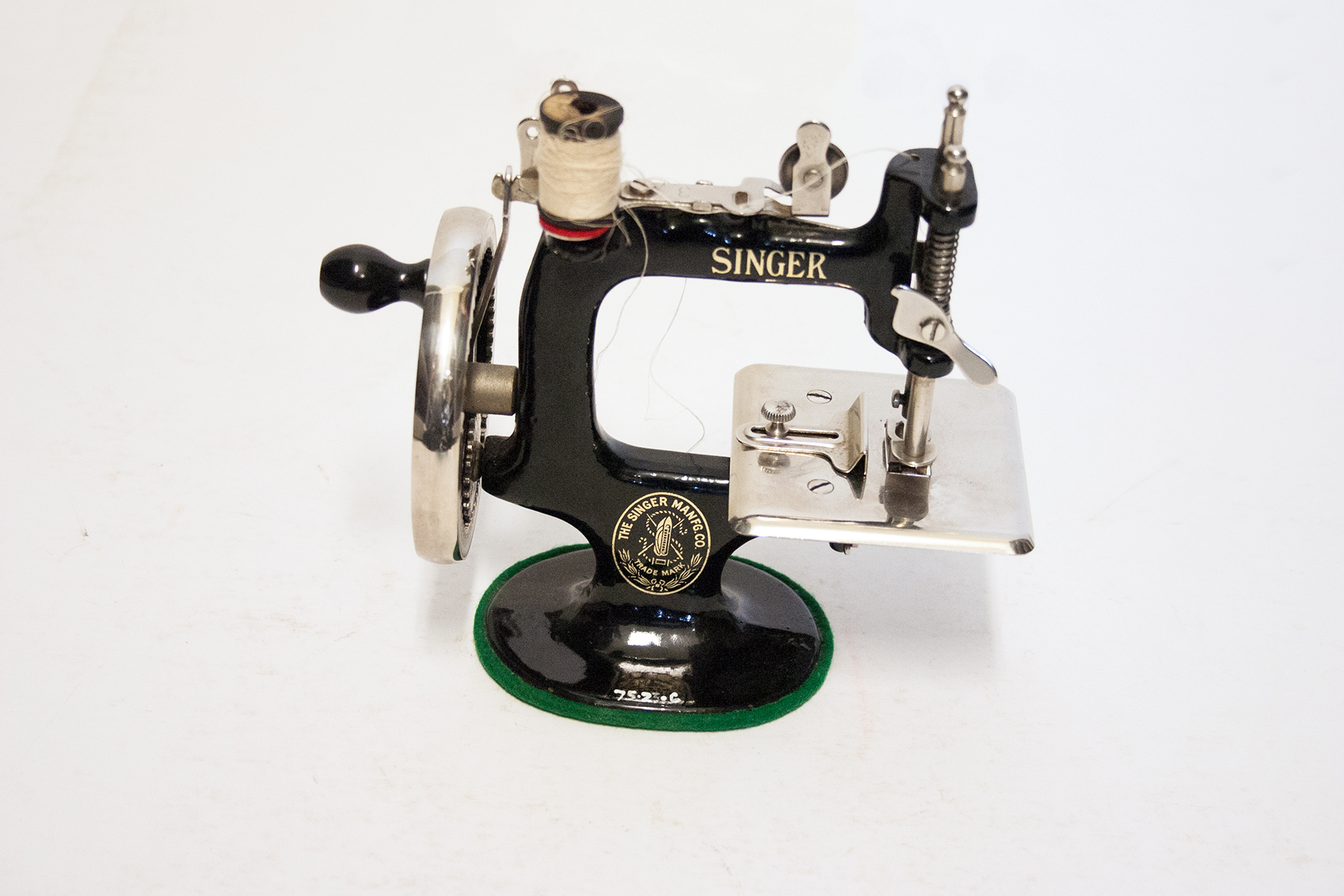 """A cast iron sewing machine that has a black body with a gold manufacturing label and text that reads """"SINGER"""" in gold letters at the top, with a green ring around the base, a metal balance wheel on the left side of the machine, a bobbin winder with white thread and thread take up on the top, and a silver bed plate and pressure bar on the right side, photographed on a plain white background"""