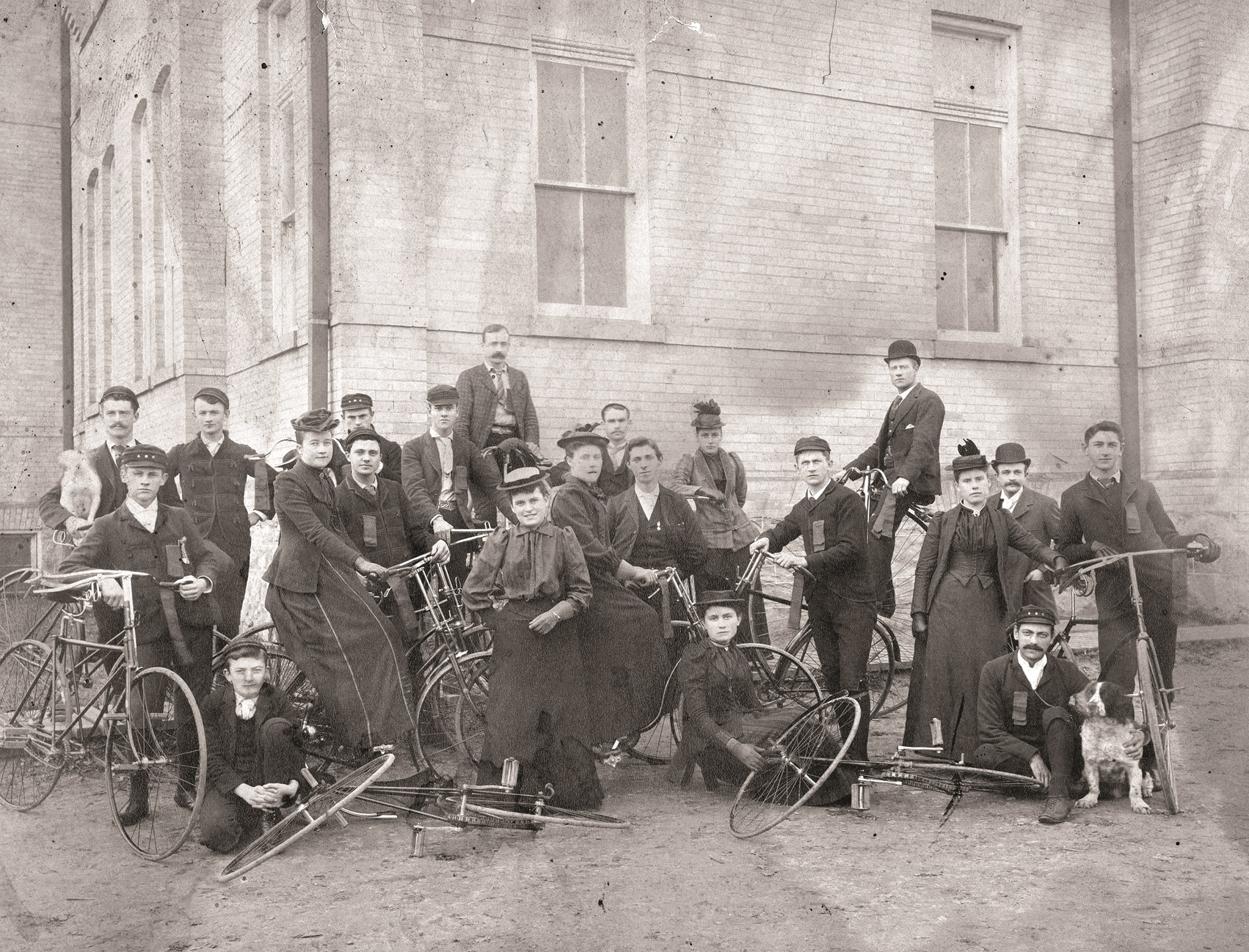 A black and white photograph of a group of men and women in late 19th century clothes posing with their bicycles in front of a large brick building.