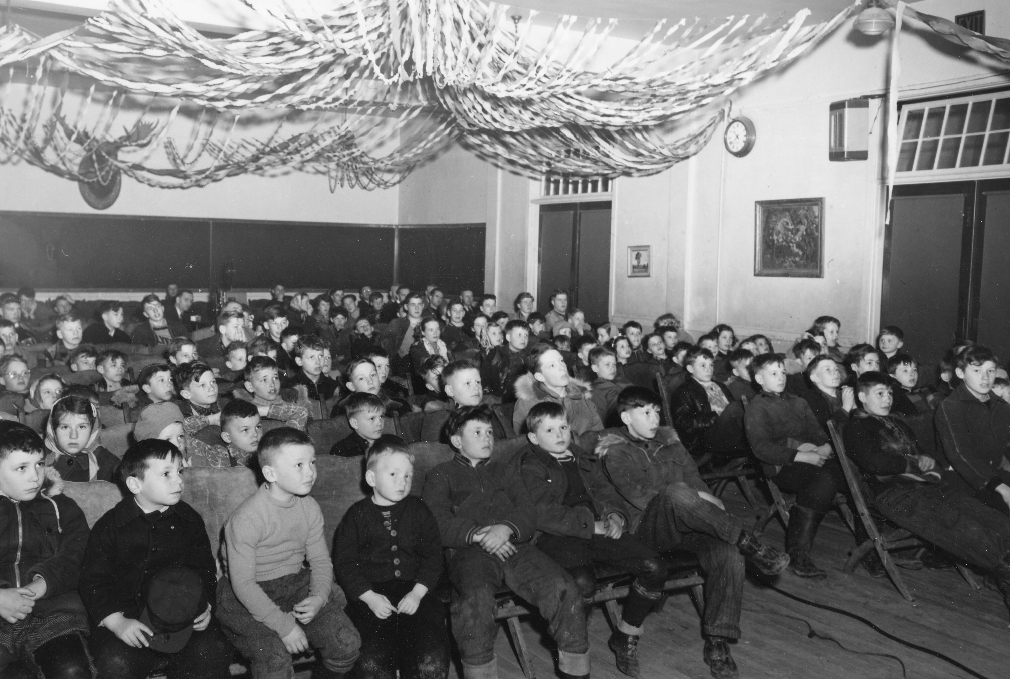 A black and white photograph of a room with dozens of small children sitting in rows on folding chairs, all looking at something off-camera. Streamers are hanging, as if draped, on the ceiling.