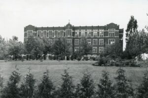 A black and white photograph of an imposing 4 storey building with many windows behind a row of trees.