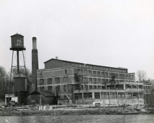 A black and white photograph of a brick industrial building with a water tower and smokestack on the left, on the bank of a body of water.