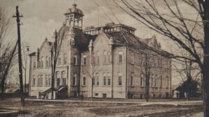 A sepia-coloured photograph of an ornately trimmed stone school building with stairs leading to large double doors and a cupola on the roof, a small group of students are standing on the stairs and around the building.