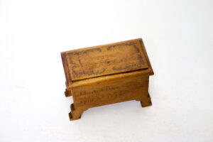 A small box carved out of wood with furniture-like feet, decorrated on the top and side with faint images and writing, photographed on a white background