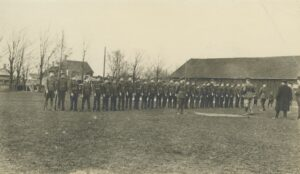 A black and white photo of soldiers lined up in a treed park, officers are inspecting them, a wooden building stands behind.