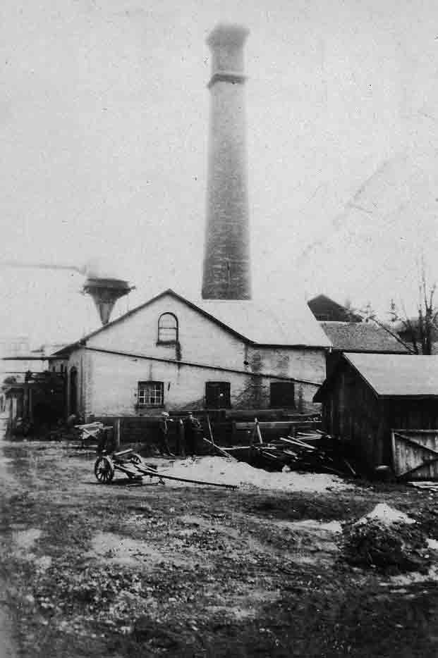 A black and white photograph of an industrial yard with a large squared smoke stack in the background.