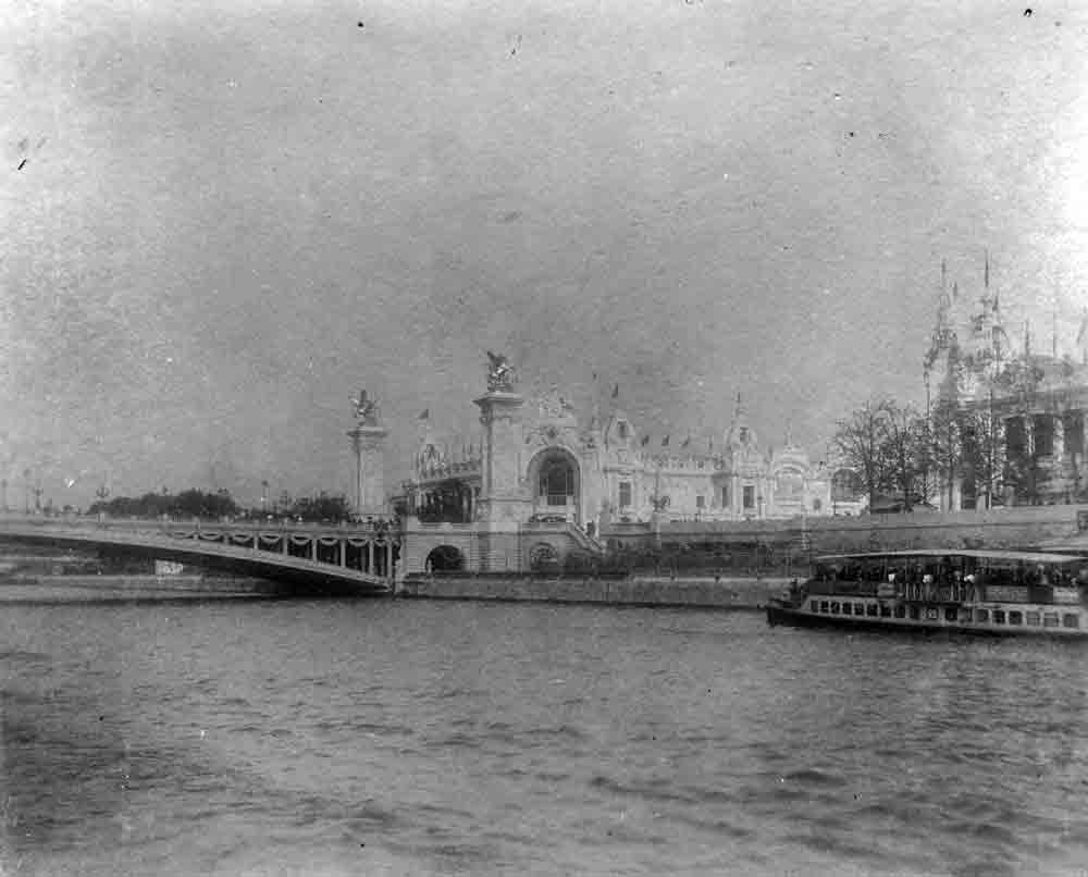A black and white photograph of an ornate exhibition building across a large river.