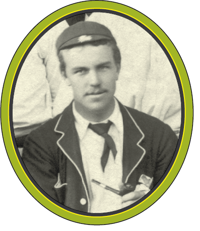 A black and white photograph of a young man with a small moustache, holding a pipe, and wearing a small cricket cap and a jacket with piped lapels.