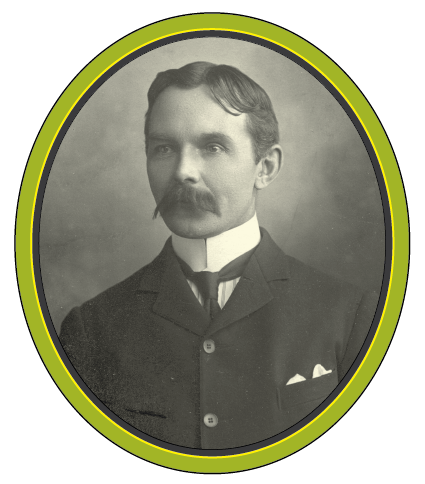 A black and white portrait photograph of a man with a long moustache and a high white collared shirt.
