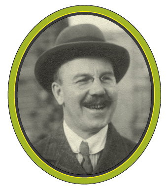 A black and white photograph of a smiling man with a moustache, glasses, and a homburg hat.