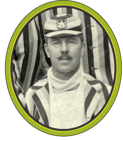 A black and white photograph of a man with a waxed moustache and rimless glasses wearing a matching striped jacket and hat, others wearing the same are behind him.
