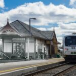 A photograph edited to combine an old and new photo of the same location: a train pulling into a train station with people waiting on the platform.