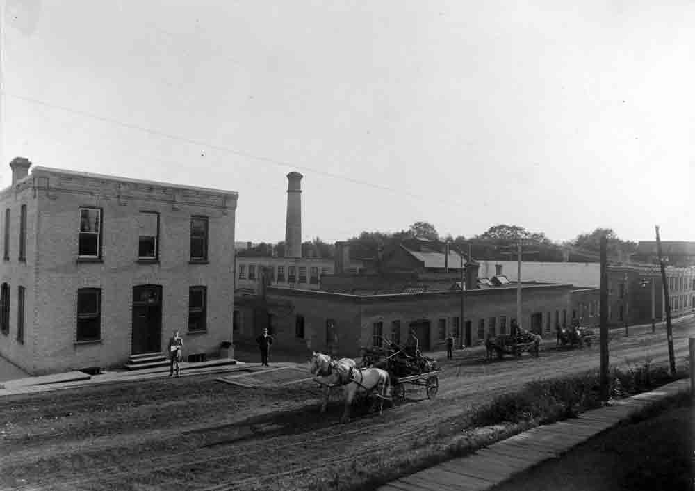 A black and white photograph of a dirt road with horse-drawn carriages and a large brick industrial complex on the far side.