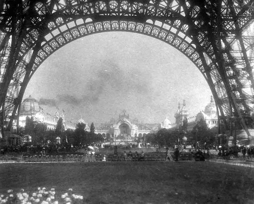 A black and white photograph taken from underneath the Eiffel Tower.