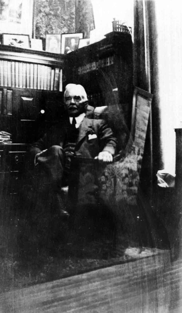 A black and white photograph of a man with white hair and a moustache sitting in a large chair against a high desk full of books.