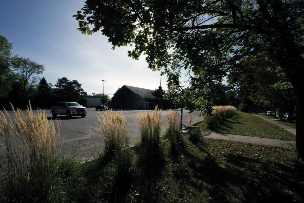 A photograph of a church parking lot bordered by tufts of tall grass.