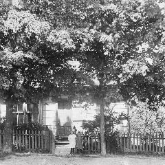 A crop of a black and white photo of two children standing at the fenced entrance to a treed yard, with a white house behind them.