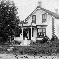 A cropped black and white photograph of an ornately trimmed house with people standing on the stairs and veranda.