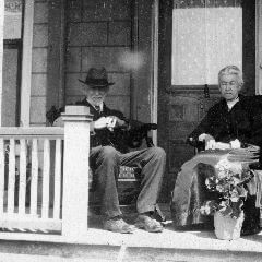 A cropped black and white photograph of an old couple sitting on their porch.